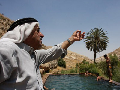 A Palestinian visitor gestures near a swimming pool of natural water at Ein Fara springs. (AFP Photo / Ahed Izhiman)