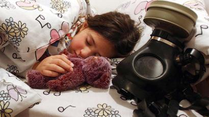 A nine-year-old girl sleeps next to her gas mask in Zur Hadasa near Jerusalem (Reuters/Nati Shohat/Flash)