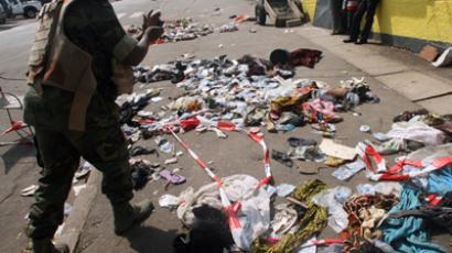 People stand next to clothing and various items spread over the pavement at the scene following a stampede in Abidjan, on January 1, 2013 (AFP Photo / Herve Sevi) (RTI video via AP)