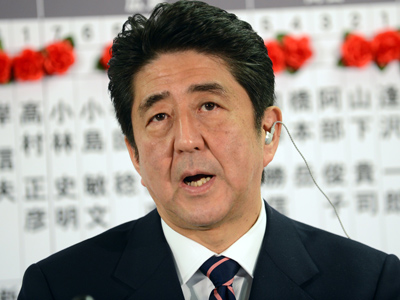 Shinzo Abe speaks during a TV interview after he put rosettes by successful general electoral candidates' names on a board at the party headquarters in Tokyo on December 16, 2012 (AFP Photo / Yoshikazu Tsuno)