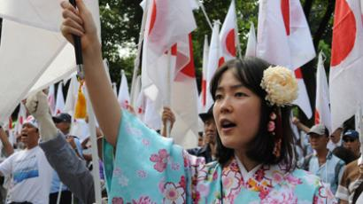 A girl in kimono dress amongst right wing acrivists raises a national flag to protest against China in Tokyo on September 22, 2012 (AFP Photo / Rie Ishi)
