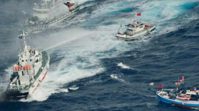 An aerial view shows Japan Coast Guard patrol ship spraying water at fishing boats from Taiwan as Taiwan's Coast Guard vessel sails near the disputed islands in the East China Sea (Reuters / Kyodo)