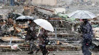 Survivors walk in the snow after checking on what was left of their properties in the tsunami devastated Kamaishi city, Iwate prefecture on March 16, 2011
