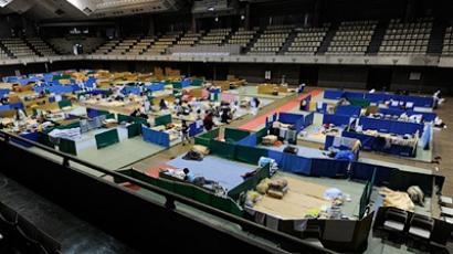 Evacuees, mainly ones who lived near the stricken Fukushima nuclear plant north of Tokyo, spend their time in small marked out spaces on tatami mats spread out over a gymnasium floor used as a shelter in Tokyo on March 29, 2011 (AFP Photo / Toru Yamanaka)