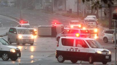 A vehicle is overturned on a road in Naha city, Okinawa prefecture on September 29, 2012. (AFP Photo / Jiji Press)