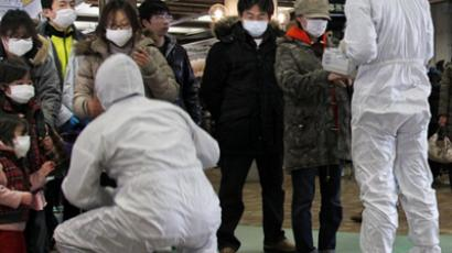 Officials in full radiation protection suits scanning evacuated people with geiger counters to check radiation levels (AFP Photo / Ken Shimizu)
