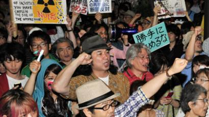 Anti nuclear activists hold placards and shout slogans during protest in front of the prime minister's official residence in Tokyo on June 22, 2012. (AFP Photo/Rie Ishii, Video by Youtube user ken23qu)