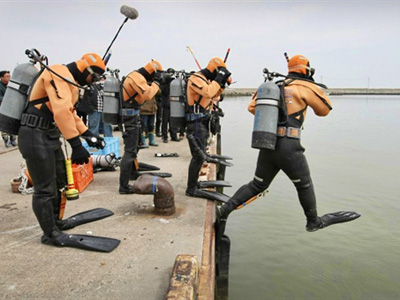 JAPAN, Natori : In a picture taken on April 7, 2011 Japan Coast Guard frogmen jump into the sea to search for missing people at a port in Natori, Miyagi prefecture, nearly a month after the March 11 earthquake and tsunami battered the northeastern coast of Japan. (AFP Photo / Jiji Press)