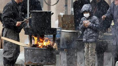 JAPAN, SENDAI : A boy (R) waits for boiled water to cook instant noodle outside a shelter in Sendai, in Miyagi prefecture on March 16, 2011.  (AFP Photo / Jiji Press)