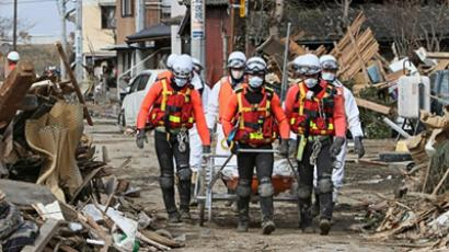 Japanese rescue team members transporting a body in the town of Watari in Miyagi prefecture on March 14, 2011 (AFP Photo / Jiji Press)