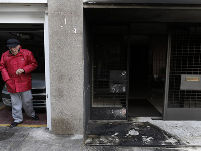 A resident stands next to the burnt entrance of a building following a series of arson attacks against journalists in Athens January 11, 2013.  (Reuters/John Kolesidis)