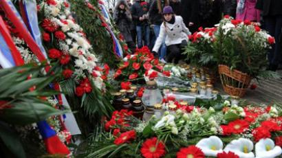 People lay floral tributes as they gather to commemorate the victims of the Smolensk presidential plane crash on the Smolensk airdrome on April 10, 2011 (AFP Photo/Natalia Kolesnikova)