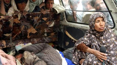 An Afghan woman is interviewed next to the body of a child killed by coalition forces in Kandahar province on March 11, 2012 (Reuters / Ahmad Nadeem)