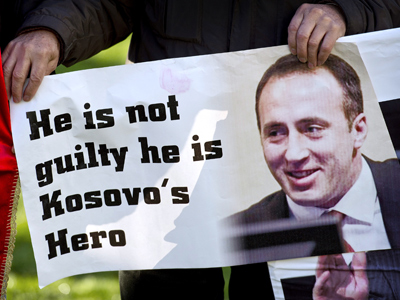 A supporter of former Prime Minister and rebel chief Ramush Haradinaj holds the latter's portrait as he celebrates outside the International Criminal Tribunal for the former Yugoslavia at the Hague on November 29, 2012 (AFP Photo / Pool / Koen Van Weel)
