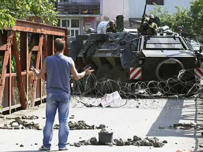 A Kosovo Serb talks to Germany's KFOR soldiers blocking the bridge during clashes in the town of Zvecan June 1, 2012. (Reuters/Bojan Slavkovic)