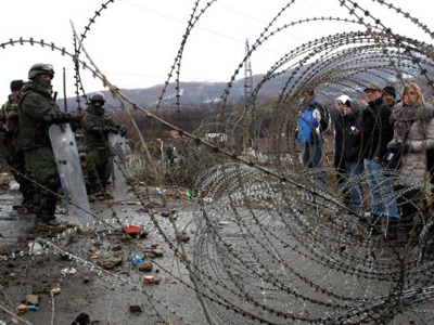 Kosovo Serbs stand by a barbed wire erected by KFOR soldier at a roadblock in Northern Kosovo (AFP Photo / Sasa Djordjevic)