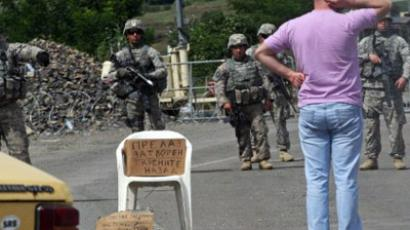 Serbia, Jarinje: A man looks at KFOR soldiers standing guard at Jarinje border crossing between Serbia and Kosovo on July 29, 2011. (AFP Photo / Sasa Djordjevic)