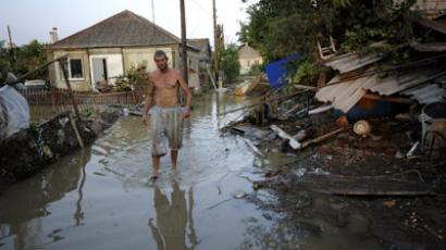 A local resident walks along a flooded street in the southern Russian town of Krymsk on July 8, 2012 (AFP Photo/Mikhail Mordasov)