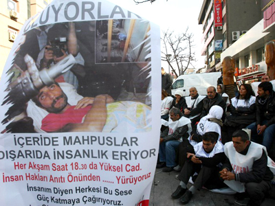 "Members of a pro-Kurdish party stand behind a banner reading ""They are dying"" as they start on November 17, 2012 a two-day hunger strike in support of the several hundreds Kurdish inmates who have been on hunger strike for 67 days in Ankara. (AFP Photo / Adem Altan)"