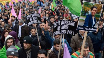 "People hold placards reading : ""This brutality will not weaken us"" during a demonstration on January 12, 2013 in Paris, two days after Cansiz and two Kurdish activits were found shot dead at Paris Kurdistan Information Bureau. (AFP Photo / Eric Feferberg)"