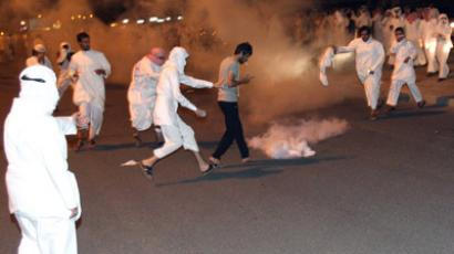 Protesters run for cover as Kuwait riot police used stun grenades and tear gas to disperse thousands of angry demonstrators who marched on the central prison where a leading opposition figure is detained, in Kuwait City on October 31, 2012. (AFP Photo/Yasser Al-Zayyat)
