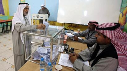 Electoral officials watch on as a Kuwaiti man casts his ballot to elect a second parliament in ten months, at a polling station in Kuwait City on December 1, 2012. (AFP Photo / Yasser Al-Zayyat)