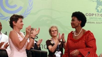 South African Foreign Affairs Minister Maite Nkoana-Mashabane (R) receives a standing ovation from Congress of Parties Executive Director Christiana Figueres and hundreds of delegates at the Climate Change Conference in Durban on December 11, 2011 (AFP Photo / RAJESH JANTILAL)