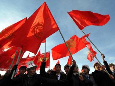 "Kyrgyz men wave flags during a rally marking the ""National Flag Day"" at the central Ala-Too square in Bishkek on March 3, 2012. (AFP Photo / Vyacheslav Oseledko)"
