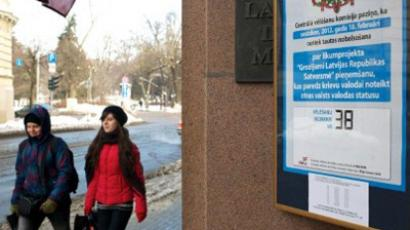 Riga: Youths walks past a sign at the entrance of a polling station in Riga on February 16, 2012, ahead of the February 19 referendum (AFP Photo/Ilmars Znotins)