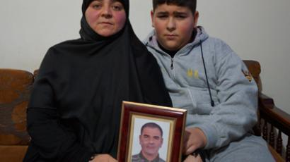 Mona Termos and her son hold a picture of their abducted husband and father. (Photo by Nadezhda Kevorkova)