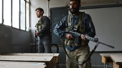 Syrian rebels take position inside a building to observe the movement of regime forces. (AFP Photo / PHilippe Desmazes)
