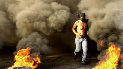 A Lebanese protester runs between burning tyres as demonstrators block a road in the southern city of Sidon on October 20, 2012 to protest against a bomb blast in the capital Beirut the day before (AFP Photo / Mahmoud Zayyat)