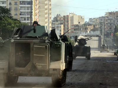 Lebanese soldiers ride in their armoured vehicle as they patrol the streets of the northern Lebanese city of Tripoli on December 5, 2012.(AFP Photo / STR)
