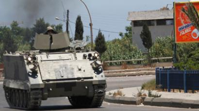 Lebanese army soldiers patrol near the Sunni Muslim Bab al-Tebbaneh neighbourhood in Tripoli, northern Lebanon, as smoke from clashes rises in the background. June 2, 2012. (Reuters/Omar Ibrahim)