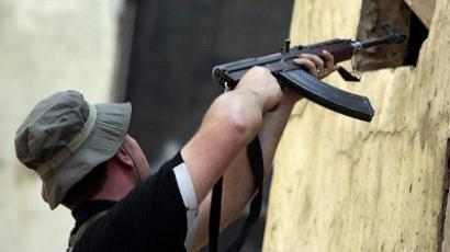A Lebanese Sunni Muslim man aims his gun through a window during fighting in the Bab al-Tebbaneh neighbourhood of the northern Lebanese city of Tripoli during the second day of clashes between factions supporting and opposed to the revolt in Syria on May 14, 2012 (AFP Photo/Joseph Eid)