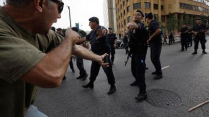 Lebanese policemen clash with angry mourners who were trying to storm the Lebanese government offices after the funeral of slain intelligence officer Wissam al-Hassan in Beirut.(Reuters / Stringer)
