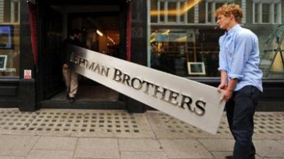 Employees pose for photographers with a Lehman Brothers company sign at Christie's auction on September 24, 2010 (AFP Photo / Ben Stansall)