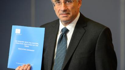 Lord Justice Brian Leveson poses with an executive summary of his report following an inquiry into media practices in central London November 29, 2012 (Reuters / Paul Hackett)
