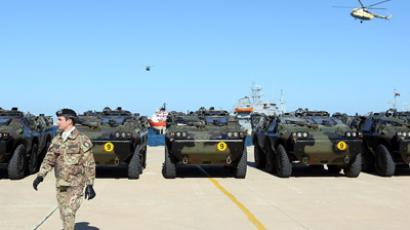 An Italian Army soldier walks by some of the twenty military vehicles during an handing over ceremony by Italy to Libya at a Libyan Navy Base on February 6, 2013, in Tripoli (AFP Photo / Mahmud Turkia)