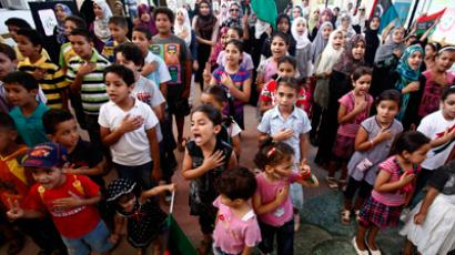 Children sing a new national anthem during the raising of the Kingdom of Libya flag at their school in Tripoli August 29, 2011 (Reuters / Zohra Bensemra)