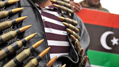 Libya: A Libyan protester shows ammunition confiscated from soldiers as another holds his country's old flag in the background in Benghazi on February 25, 2011. (AFP Photo / Patrick Baz)