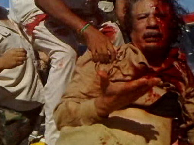 A National Transitional Countil (NTC) fighter pulls Libya's former leader Muammar Gaddafi onto a miltary vehicle in Sirte in this still image taken from video shot on October 20, 2011 and released on October 22, 2011 (Reuters/Reuters TV)