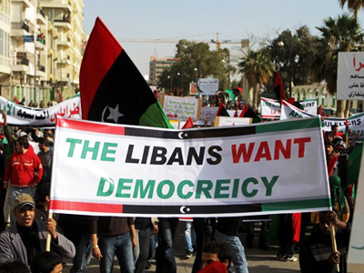 Libyan rebels hold up placards and flags as thousands of people gathered in the streets of Benghazi on March 23, 2011 to show their support for an internationally-enforced no-fly zone over Libya (AFP Photo / Patrick Baz)