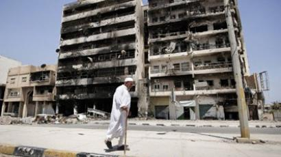 "Misrata : An elderly Libyan man walks past damaged buildings in Tripoli Street in the Libyan port city of Misrata on June 23, 2011 as Libyan leader Moamer Kadhafi said he did not fear death and defiantly vowed to fight ""to the beyond"". (AFP Photo/Gianluigi Guercia)"