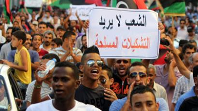 "Libyan demonstrators hold a sign reading ""People don't want militias"" as thousands of people march in Benghazi during a protest against militias on September 21, 2012 (AFP Photo / Abdulah Doma)"