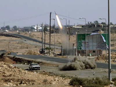 Files picture dated September 22, 2011 shows Libyan National Transitional Council (NTC) fighters launching a rocket towards Bani Walid from their outpost at the entrance of the city (AFP Photo / Joseph Eid)