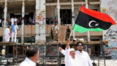 A Libyan elderly man waves the rebellion's flag as residents of Tripoli tour the destroyed Bab al-Aziziyah former headquarters of Libyan leader Moamer Kadhafi on September 1, 2011, as rebel forces freshly installed in Tripoli braced for possible attacks from the remnants of Kadhafi's supporters on the 42nd anniversary of his rise to power (AFP Photo / Mahmud Turkia)