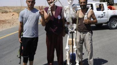 Libyan rebel fighters pose with a skeleton meant to represent fugitive Libyan leader Moamer Kadhafi and erected by Libyan rebel fighters stands on the road at a check point on September 1, 2011 in Umm Qandil, east of Sirte (AFP Photo / Eric Feferberg)