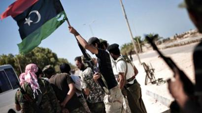 Libya, Brega: Libyan rebels, one holding up the adopted pre 1969 flag, as they manage a check point at the entrance of the residential area of Brega, on August 15, 2011, as battles between rebel forces and those loyal to Libyan leader Moamer Kadhafi continue west of the town. (AFP Photo / Gianluigi Guercia)