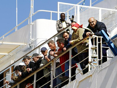 Passengers watch from the German-chartered ferry Santorini Express after it berthed with some 500 oil workers of various nationalities from the Benghazi area of Libya on board in Valletta's Grand Harbour March 1, 2011